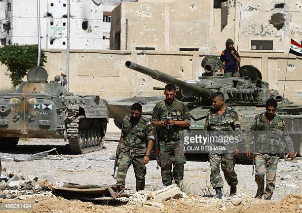 Syrian government soldiers walk near tanks parked in front of damaged buildings in Adra northeast of the capital Damascus on September 25 2014 Syrian...