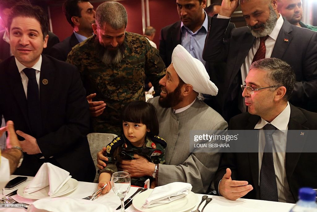 Syrian Grand Mufti Ahmed Hassun (C) attends the reception of a group wedding ceremony consisting of twenty couples made up of government soldiers and their brides in Damascus on April 29, 2014.