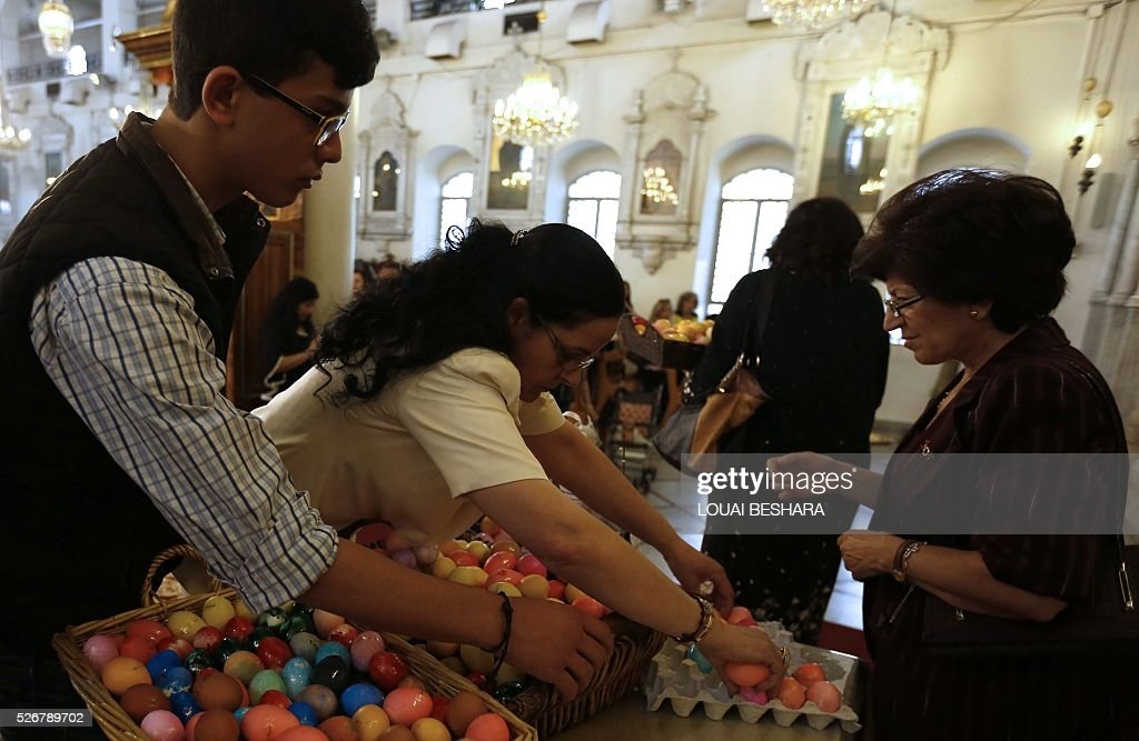 Syrian Greek Orthodox Christians arrange easter-eggs at a church in the capital Damascus during the easter procession on May 1, 2016. / AFP / LOUAI