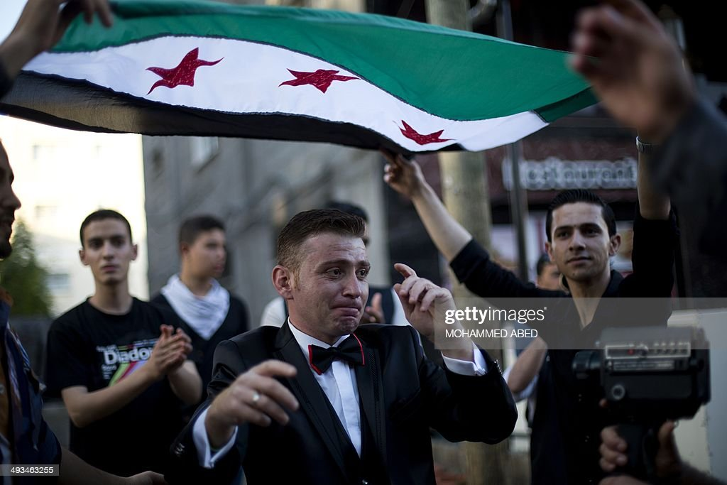 Syrian groom Waref Hameedo dances under the pre-Baath Syrian flag, now used by the Syrian opposition, during his wedding ceremony in Gaza City on May 23, 2014. Waref, who now works as a chef in a restaurant after leaving his war-torn country nearly two years ago, met his Palestinian bride Maha Abo-Alkas, who is a journalist, as she was covering events in the strip. AFP PHOTO/MOHAMMED ABED