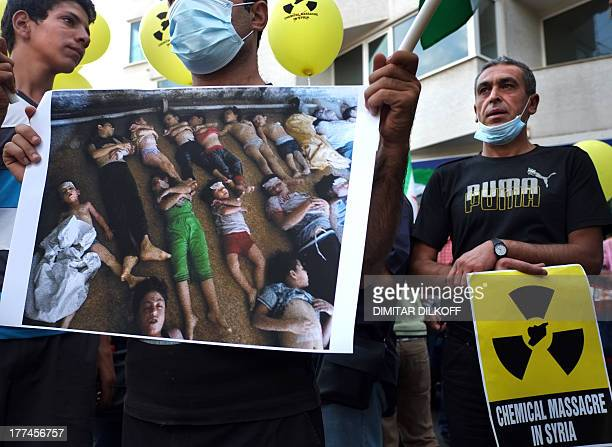 Syrian immigrants living in Bulgaria hold a photo showing the bodies of men women and children allegedly killed in a chemical attack east of Damascus...