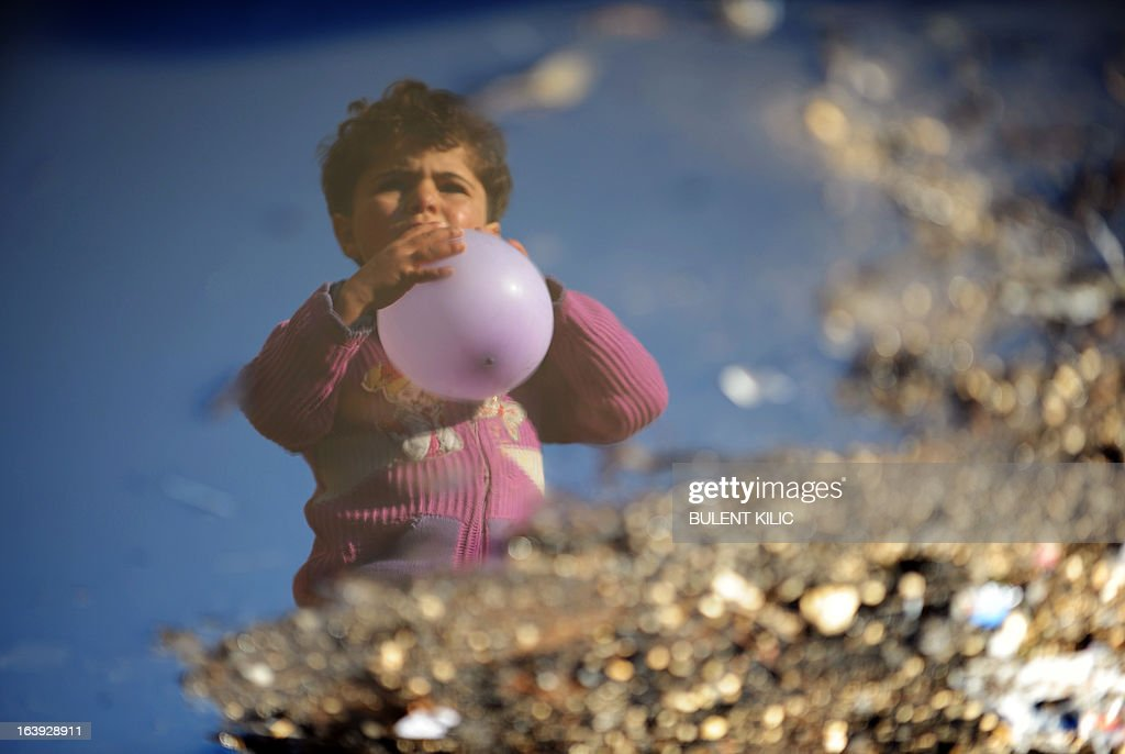 A Syrian internally displaced child holding a balloon is reflected in a puddle of water in the Bab al-Hawa camp along the Turkish border in the northwestern Syrian province of Idlib, on March 18, 2013. The conflict in Syria between rebel forces and pro-government troops has killed at least 70,000 people, and forced more than one million Syrians to seek refuge abroad.