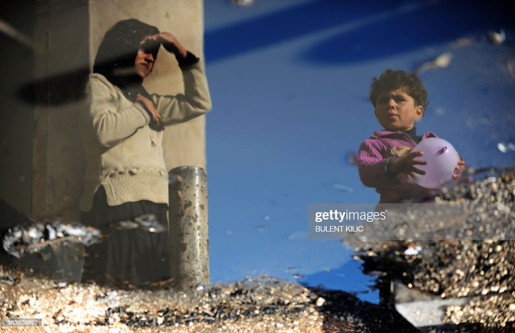 A Syrian internally displaced woman and child are reflected in a puddle of water in the Bab al-Hawa camp along the Turkish border in the northwestern Syrian province of Idlib, on March 18, 2013. The conflict in Syria between rebel forces and pro-government troops has killed at least 70,000 people, and forced more than one million Syrians to seek refuge abroad. AFP PHOTO/BULENT KILIC