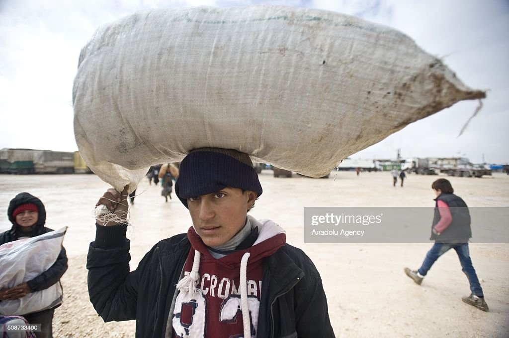 A Syrian kid, fled from his home due to Russian and Assad Regime forces attacks, carries a sacm on the way between Aleppo and Azez to arrive Turkish border, in Syria on February 6, 2016.