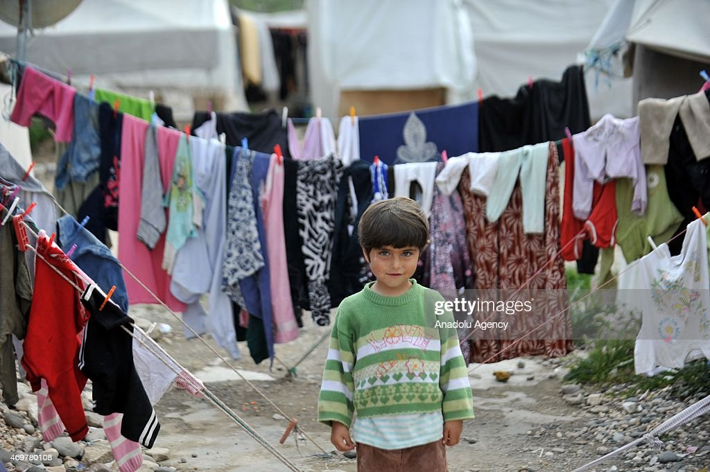 Syrian kid fled from the civil war living in a refugee camp is seen in front of laundry hanging on line in Nizlip district of Gaziantep Turkey on...
