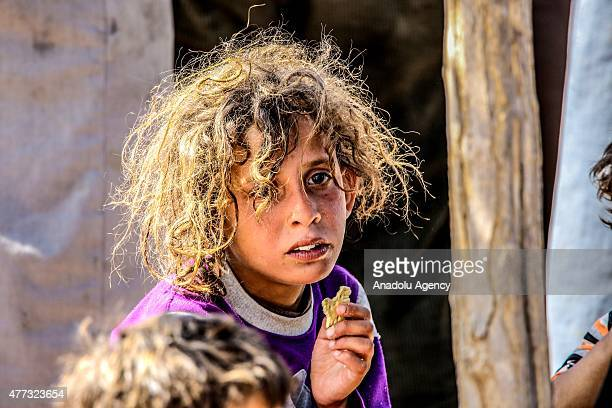 Syrian kid holds a biscuit as Syrians fleeing the clashes in the city of Tal Abyad cross into Turkey from the borderline in Akcakale district of...