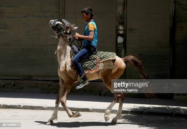 Syrian kid rides a horse at the childrens park installed by Civil defense during the Eid alFitr at Arbin town in Damascus Syria on June 27 2017