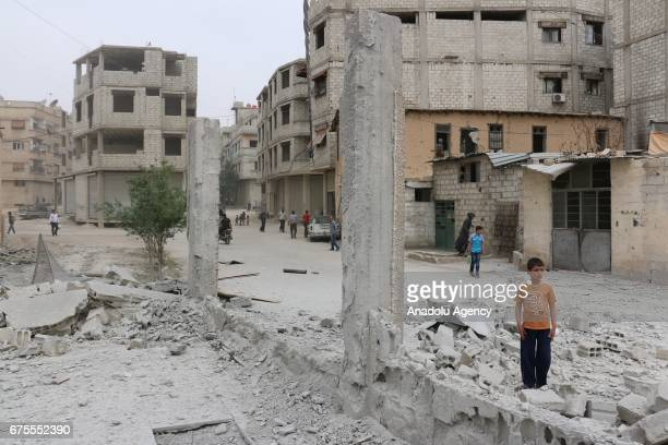 Syrian kid stands near damaged building after Assad Regime's airstrike hit residential areas at the Saqba town of Eastern Ghouta in Damascus Syria on...