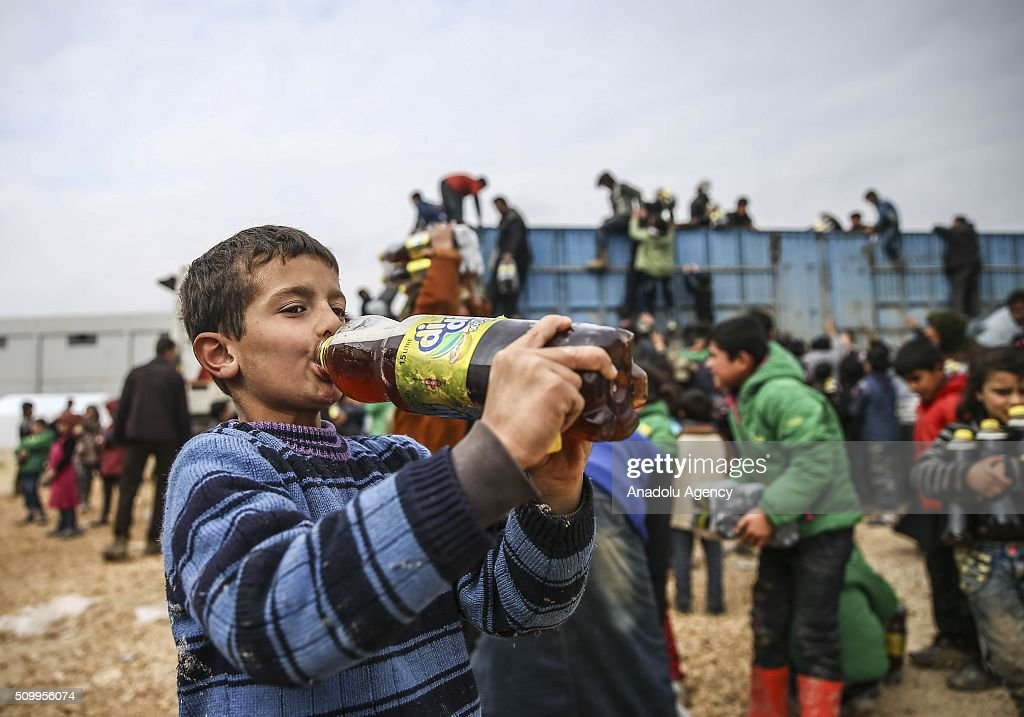 A Syrian kid, who fled bombing in Aleppo, drinks a beverage distributed by Turkish Humanitarian organization at a tent city close to the Bab al-Salam border crossing on Turkish-Syrian border near Azaz town of Aleppo, Syria on February 13, 2016. Russian airstrikes have recently forced some 40,000 people to flee their homes in Syrias northern city of Aleppo.