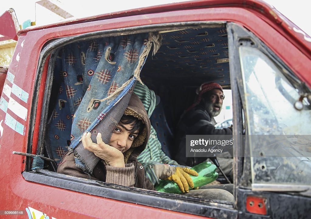 A Syrian kid, who fled bombing in Aleppo, gestures inside of a car at a tent city close to the Bab al-Salam border crossing on Turkish-Syrian border near Azaz town of Aleppo, Syria on February 13, 2016. Russian airstrikes have recently forced some 40,000 people to flee their homes in Syrias northern city of Aleppo.