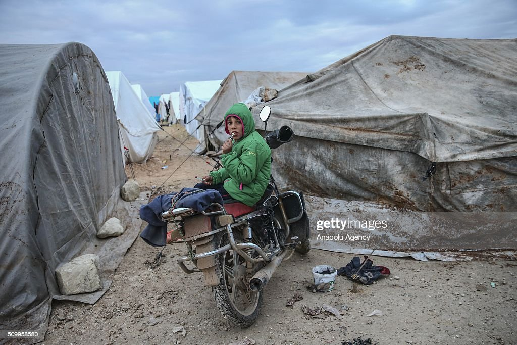 A Syrian kid, who fled bombing in Aleppo, sits on a motorcycle at a tent city close to the Bab al-Salam border crossing on Turkish-Syrian border near Azaz town of Aleppo, Syria on February 13, 2016. Russian airstrikes have recently forced some 40,000 people to flee their homes in Syrias northern city of Aleppo.