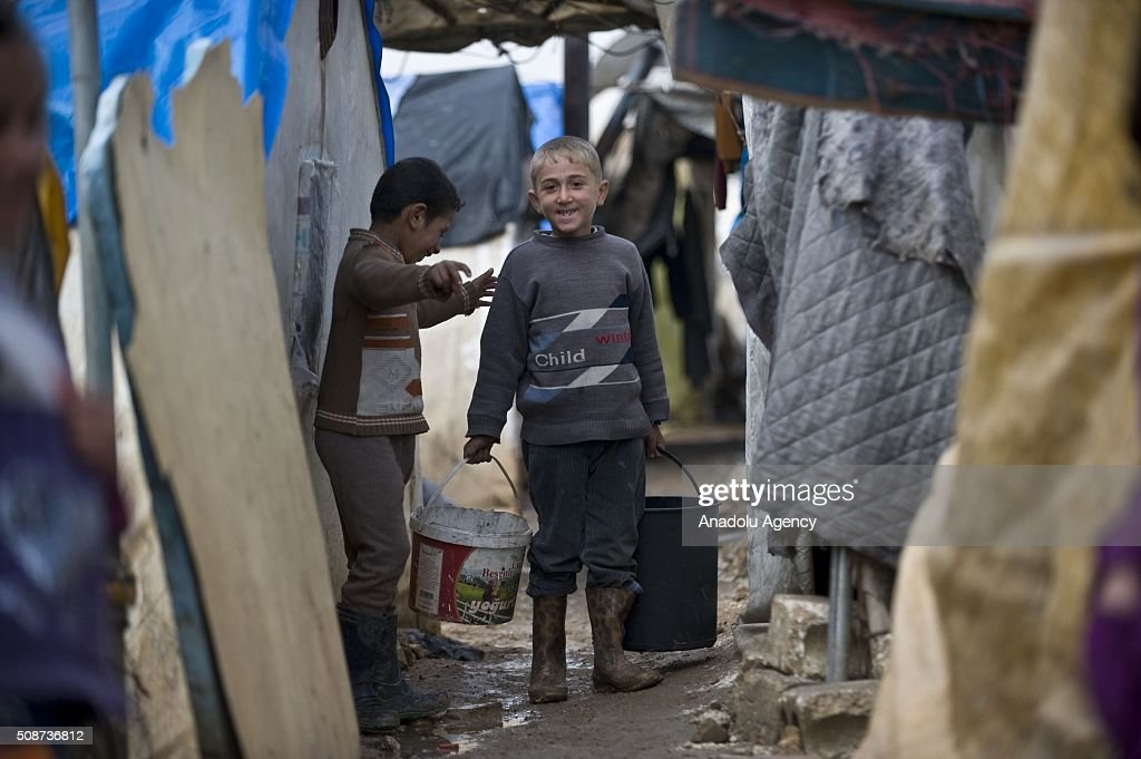 Syrian kids are seen at tent city built by IHH Humanitarian Relief Foundation near the Bab al-Salam border gate on Turkey's border in Azez district of Aleppo as they flee to Turkey to escape heavy Syrian regime and Russian airstrikes, on February 6, 2016.