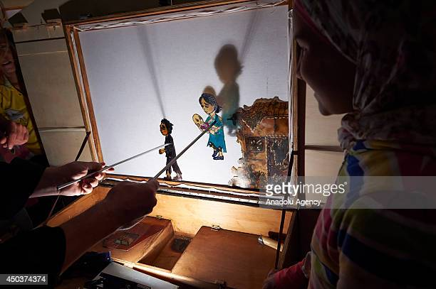 Syrian kids cheer up by the shadow puppetry that animates Syrian children who have fled their country's civil war staged by General Art Director in...