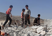 Syrian kids collect the remains from the rubble of a destroyed house following the USled coalition's airstrikes against the Islamic State of Iraq and...