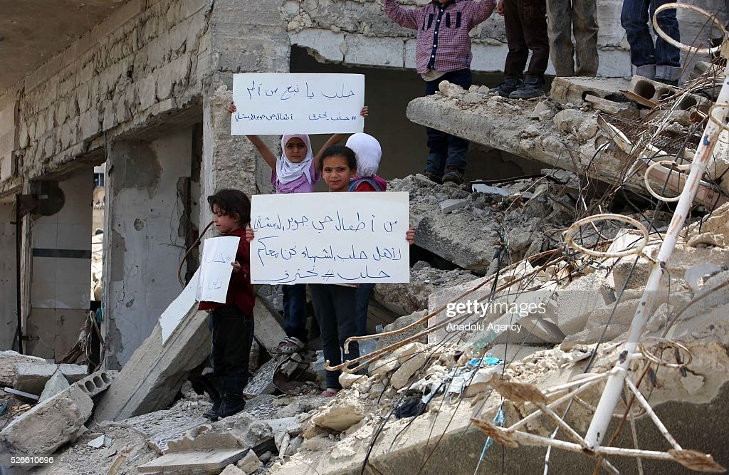 Syrian kids gather around the rubbles of houses at Damascus' Cobar region to protest against Assad Regime forces' air attacks targeting Aleppo on...