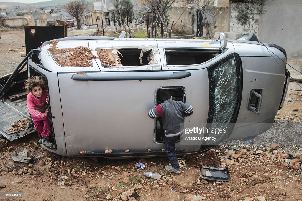 Syrian kids in a destroyed car seen in center of the Syrian town of Kobani (Ayn al-Arab), Aleppo on February 18, 2015 after it has been freed from Islamic State of Iraq and the Levant (ISIL) forces. While civilians in the eastern parts of the city are refusing entrance to the area on suspicion of a trap, houses in other areas are being presented ready for use by their owners.