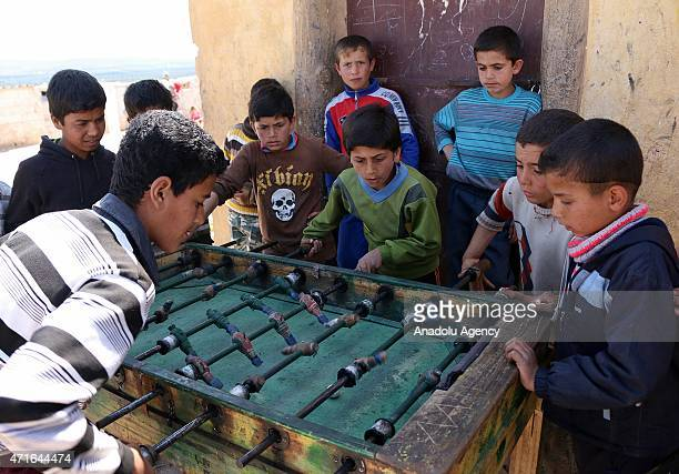 Syrian kids play foosball also known as table soccer in Atma Refugee Camp in Atma village of Idlib Syria on April 30 2015 Syrians children fled with...