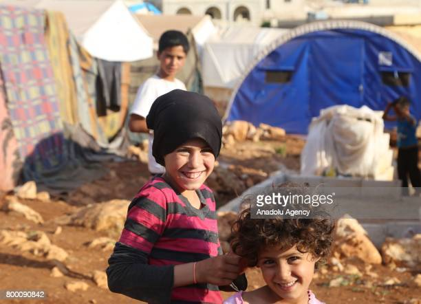 Syrian kids pose outside of tents during Muslim's holy month of Ramadan in Idlib Syria on June 23 2017 Ahead of Eid al Fitr Syrian people who fled...