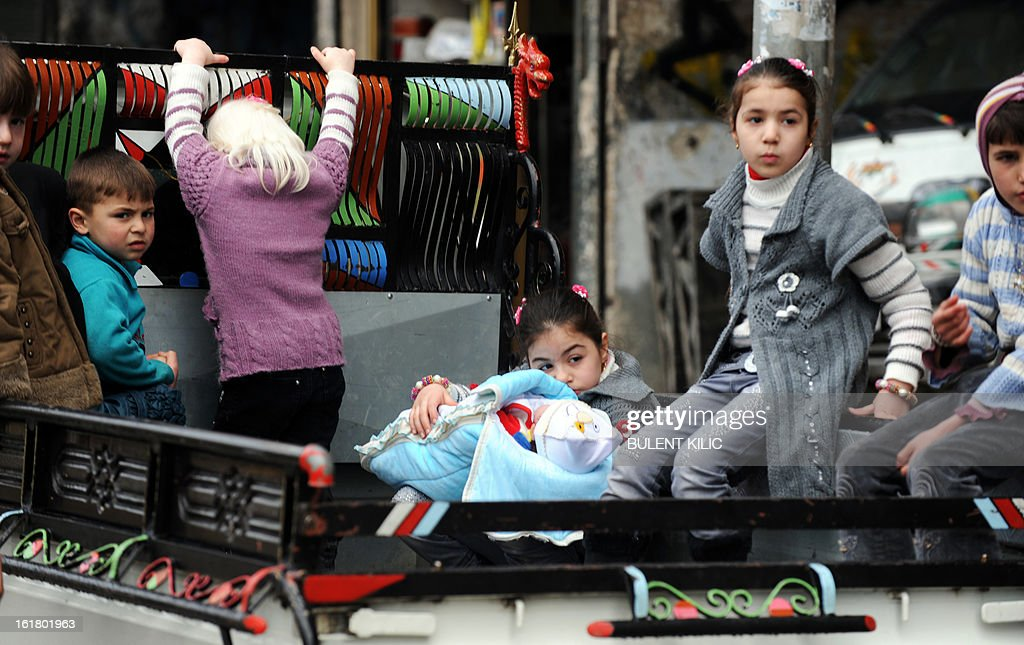 Syrian kids ride in the back of turck in the Salaheddine neighbourhood of Aleppo on February 16, 2013. More than 300 people were abducted by armed groups in northwestern Syria over two days in an unprecedented string of sectarian kidnappings, a watchdog and residents said. AFP PHOTO/BULENT KILIC