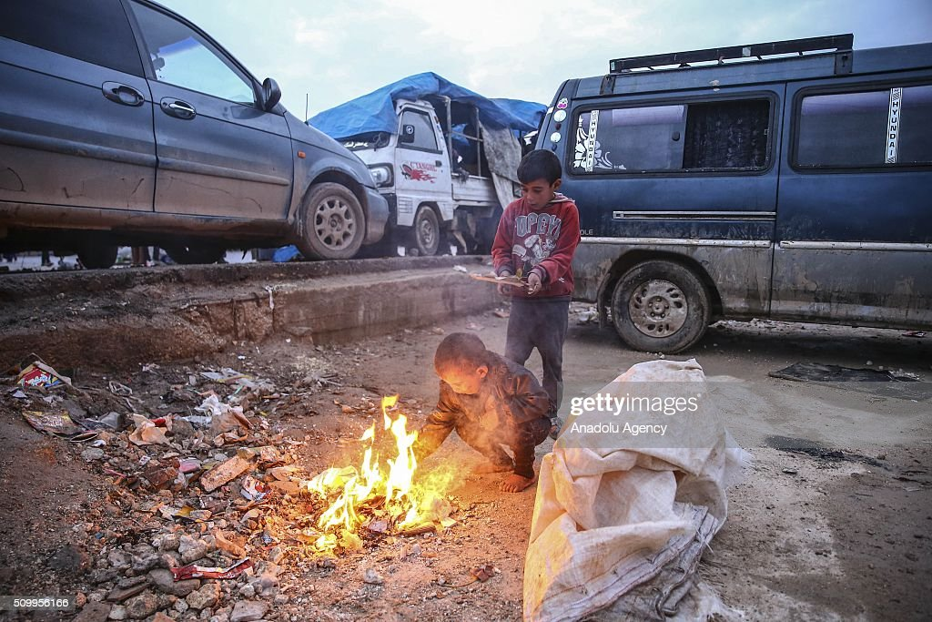 Syrian kids, who fled bombing in Aleppo, warm around the fire at a tent city close to the Bab al-Salam border crossing on Turkish-Syrian border near Azaz town of Aleppo, Syria on February 13, 2016. Russian airstrikes have recently forced some 40,000 people to flee their homes in Syrias northern city of Aleppo.