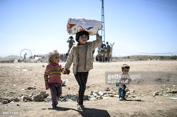 Syrian Kurd children carry their belongings after they crossed the border between Syria and Turkey near the southeastern town of Suruc in Sanliurfa...