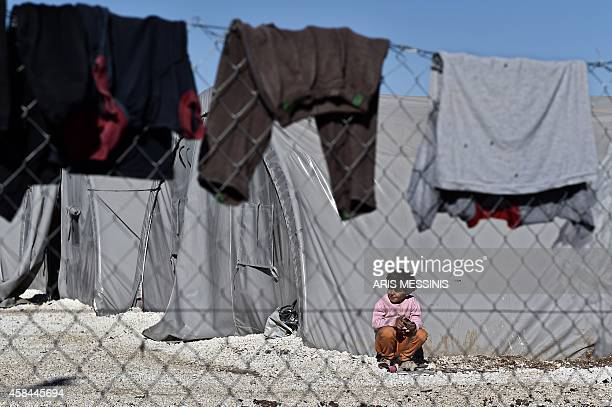 A Syrian Kurdish boy is seen behind clothes drying sits outside a tent at a refugee camp in the town of Suruc Sanliurfa province on November 5 2014...