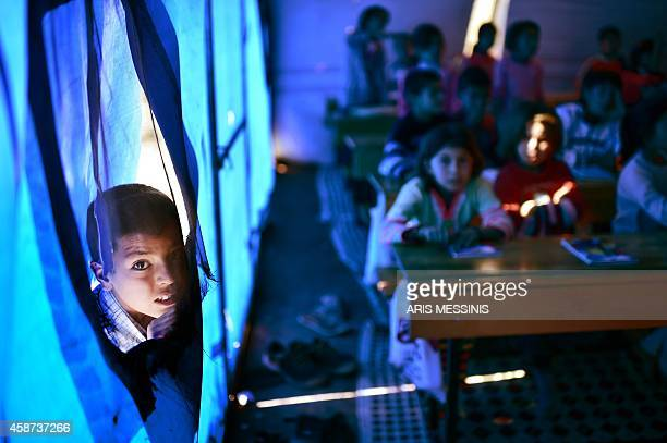 A Syrian Kurdish boy peers as children take lessons on November 10 2014 in a makeshift school tent in a refugee camp in the town of Suruc Sanliurfa...