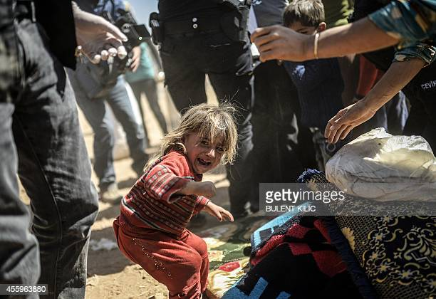 A Syrian Kurdish child cries as Turkish police search their bags after crossing the border between Syria and Turkey at the southeastern town of Suruc...