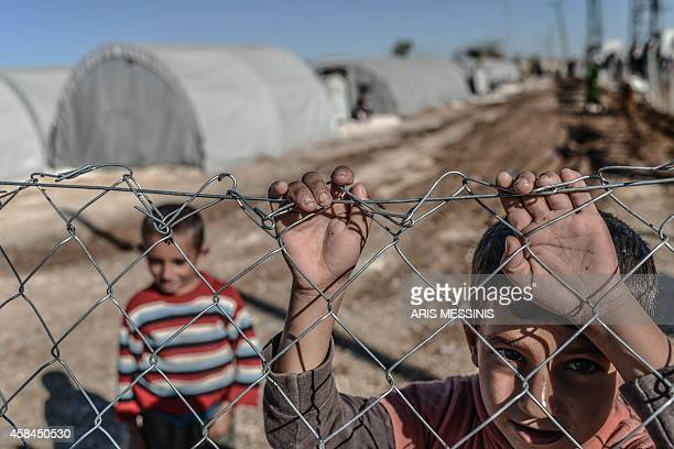 A Syrian Kurdish child looks through the fence of a refugee camp in the town of Suruc Sanliurfa province on November 5 2014 The advance of Islamic...
