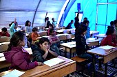 Syrian Kurdish children take lessons on November 10 2014 in a makeshift school tent in a refugee camp in the town of Suruc Sanliurfa province...