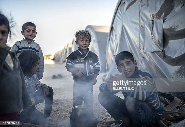 Syrian Kurdish children try to get warm around the fire early in the morning in a refugee camp at Suruc in the Sanliurfa province on October 21 2014...