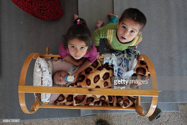Syrian Kurdish refugee children feed their newborn sister in a camp near the southeastern Turkish town of Suruc in Sanliurfa province October 1 2014...