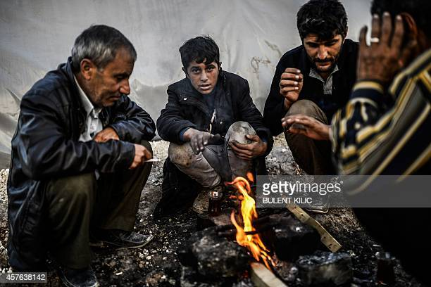 Syrian Kurdish refugees gather on October 22 2014 around a fire in the Rojava camp in Suruc in Sanliurfa province Turkey said on October 21 that...