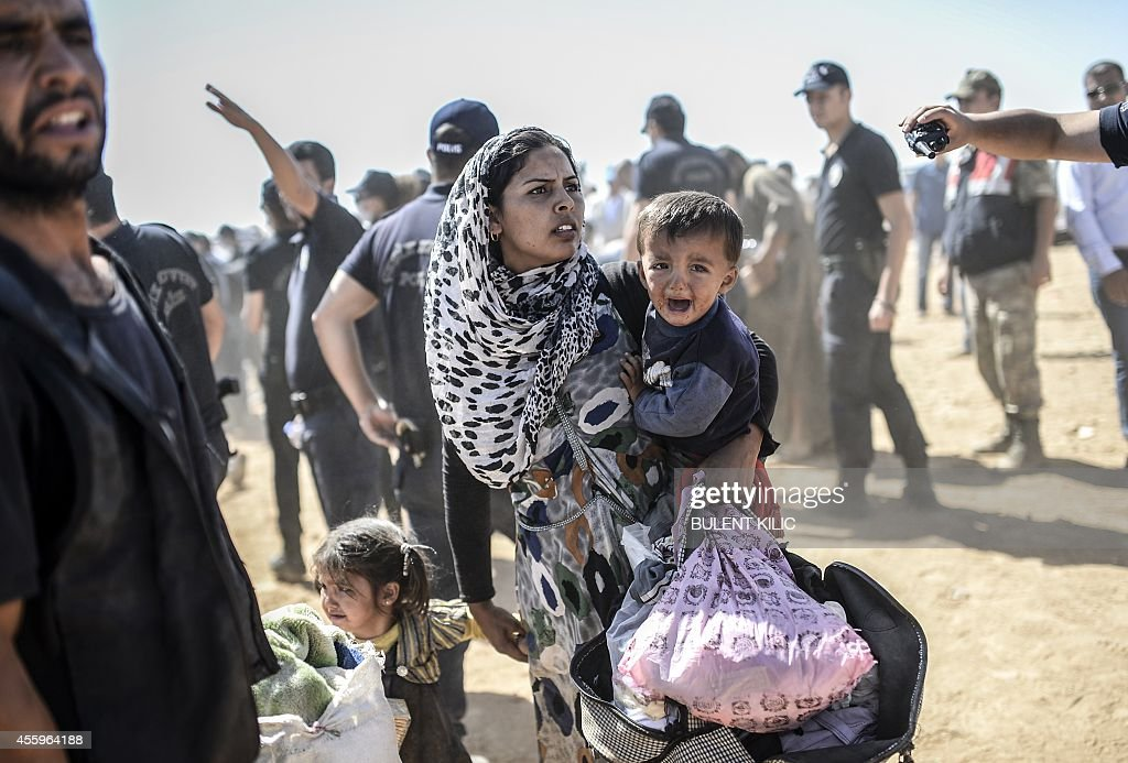 A Syrian Kurdish woman crosses the border between Syria and Turkey at the southeastern town of Suruc in Sanliurfa province on September 23 2014 The...