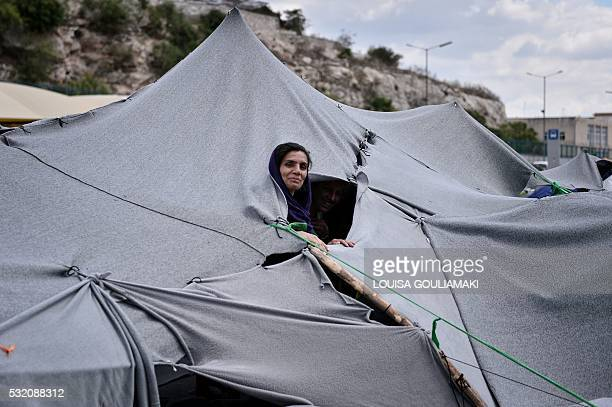 A Syrian Kurdish woman peers out from a makeshift tent made from blankets at the port of Piraeus where some 1500 refugees live at makeshift camps or...