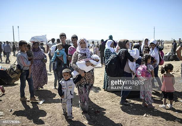 Syrian Kurds carry their belongings on September 20 2014 after crossing the border from Syria into Turkey near the southeastern town of Suruc in...