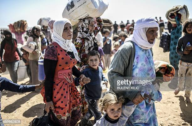 Syrian Kurds cross the border between Syria and Turkey at the southeastern town of Suruc in Sanliurfa province on September 23 2014 The UN refugee...