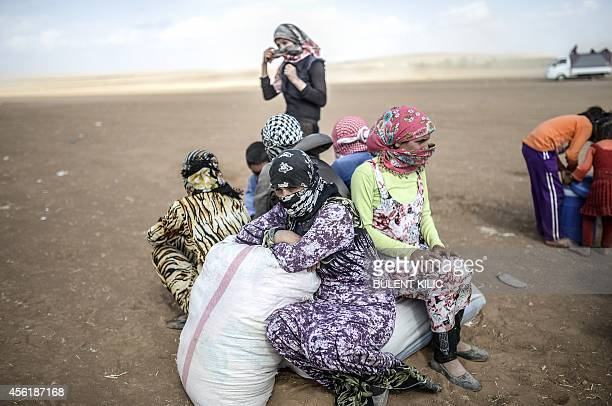 Syrian Kurds fleeing an onslaught by the jihadist Islamic State group sit on their belongings as they cross the border between Syria and Turkey at...