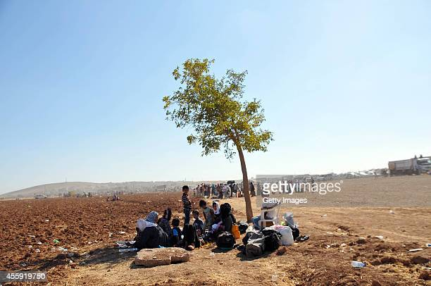 Syrian Kurds rest after crossing in to Turkey near the Syrian border September 21 2014 near the southeastern town of Suruc in Sanliurfa province...