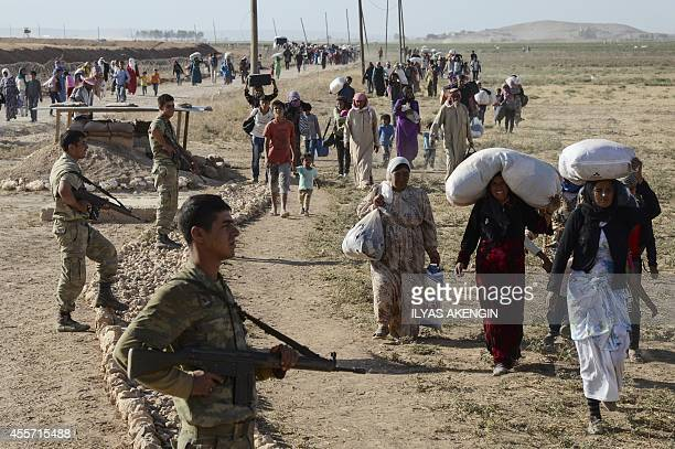 Syrian Kurds walk by Turkish soldiers after crossing into Turkey near the southeastern town of Suruc in Sanliurfa province on September 19 2014...