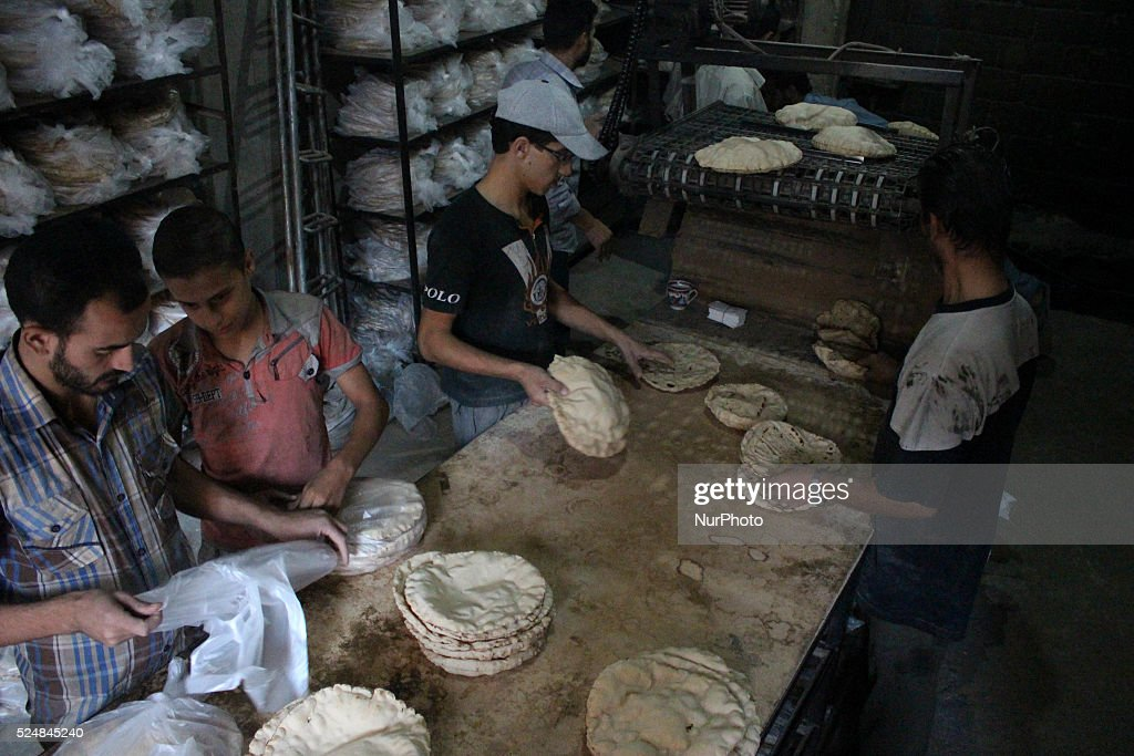Syrian labourers prepare dough to make bread at a bakery The furnace was restarted a short time ago because of the high cost of fuel and the price of...