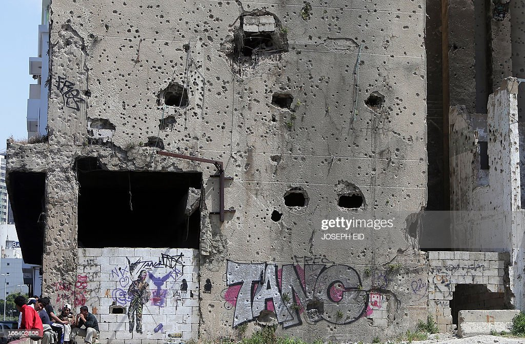 Syrian labourers sit next to a bullet riddled building dating back to the Lebanese Civil War that stretched from 1975 to 1990, in the capital Beirut.