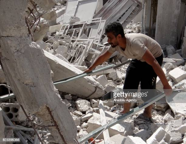 Syrian lifts the debris of a building in Daraa Syria on July 27 2017 Syrians started to return their homes after Assad regime forces stopped...
