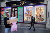 Syrian Lutfi AlHabbal carries customer purchases in front of his shop named 'Orient Video' at Sonnenallee in Neukoelln district on November 02 2013...