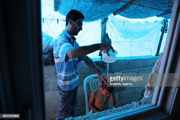 Syrian man Abdo alHamdo fled from Syria due to ongoing civilwar gives his child a bath in Turkey's Syrian border city Hatay on August 22 2016 Abdo...