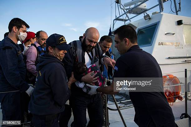 Syrian man and a child are helped from a Greek Coastguard vessel after being escorted into the harbour on June 04 2015 in Kos Greece Many migrants...