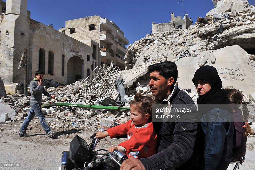 A Syrian man and his family drives past damaged buildings on a motorcycle in Maarat al-Numan, in the northwestern province of Idlib, on March 20, 2013. The number of Syrian refugees, already past the million mark, could double or triple by the end of the year if no solution is found to the conflict, the UN High Commissioner for Refugees Antonio Guterres said earlier this month.