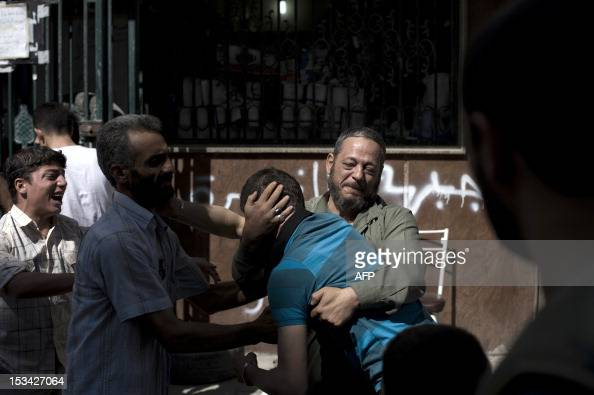 A Syrian man and his son mourn the loss of their relatives killed in the shelling on a refugee center by government forces at the Dar alShifa...