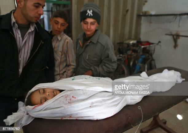 A Syrian man and two boys look at the body of a girl in a morgue who died during a reported air strike in the rebelheld besieged town of Arbin in the...