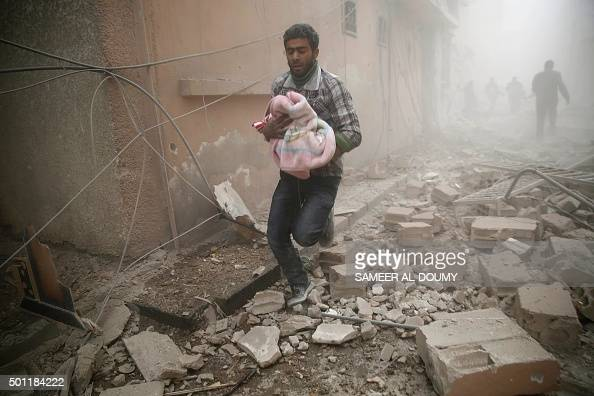 Syrian man carries a baby wrapped in a blanket following air strikes on the town of Douma in the eastern Ghouta region a rebel stronghold east of the...